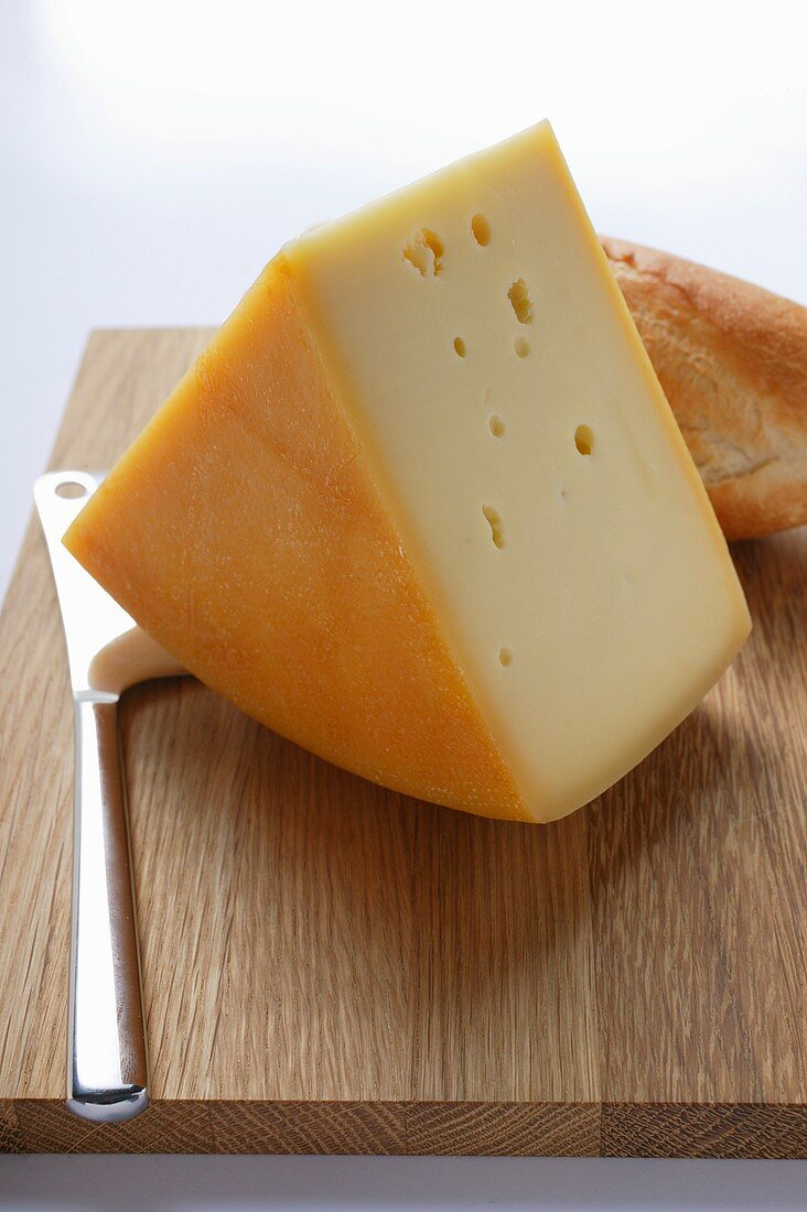 Piece of Bergkäse with baguette on chopping board