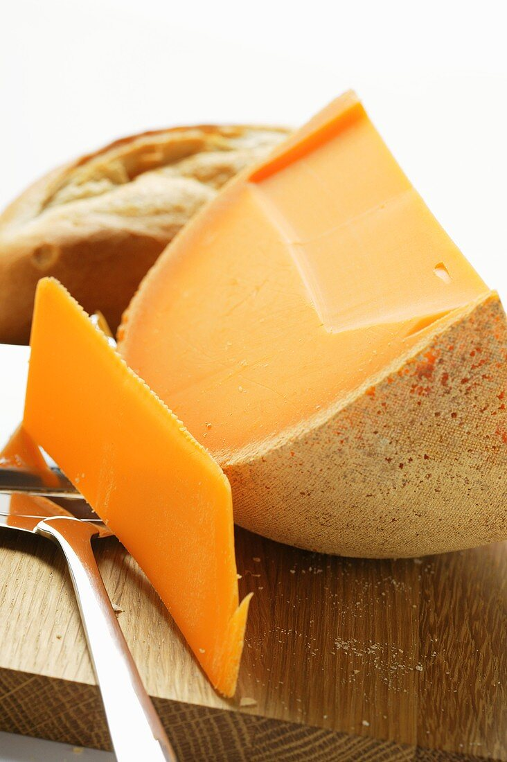 Cheddar with cheese slicer on chopping board