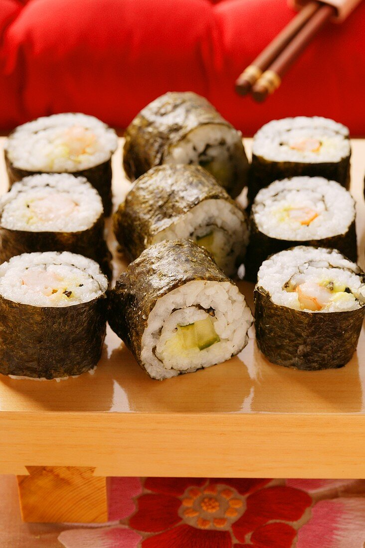 Maki-sushi platter in front of red cushion (close-up)