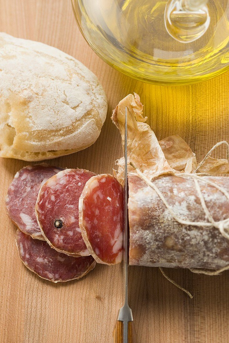 Italian salami with slices cut, white bread, olive oil