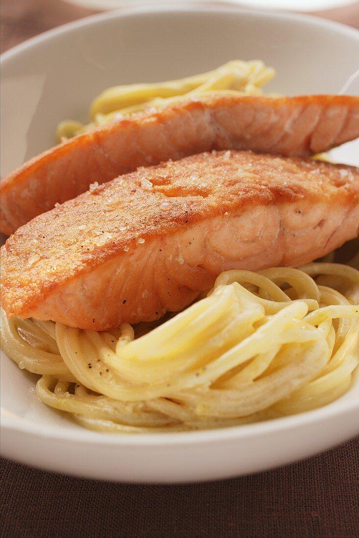 Fried salmon fillets on spaghetti