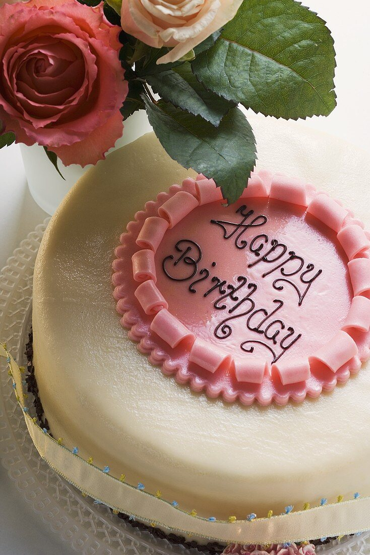 Birthday cake with the words 'Happy Birthday', roses