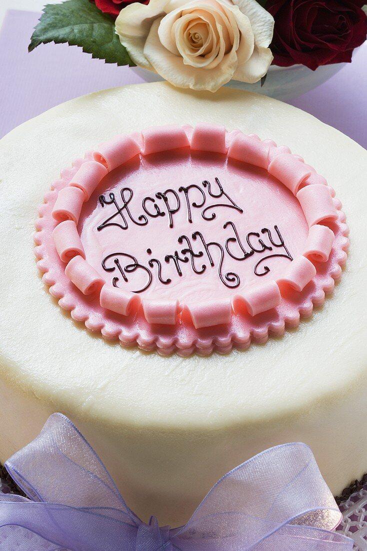 Birthday cake on pale purple box, roses (close-up)