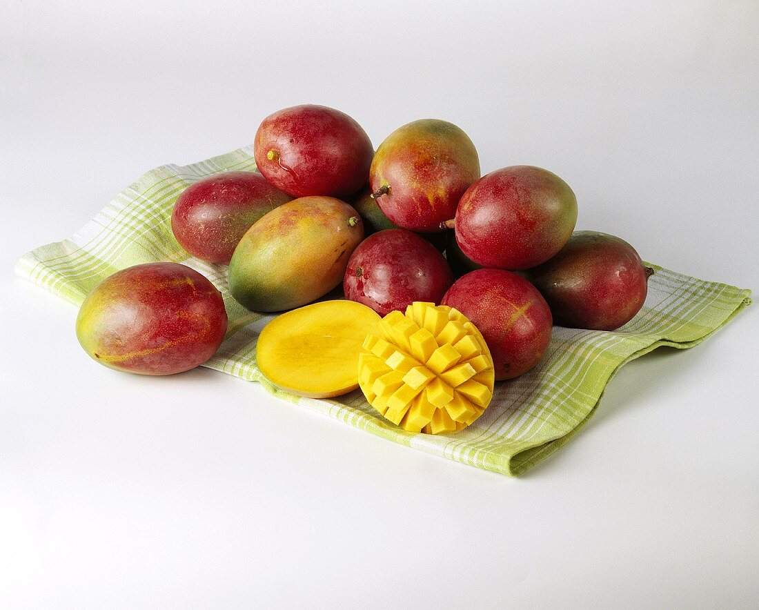 Mangos on green kitchen cloth, one cut into cubes