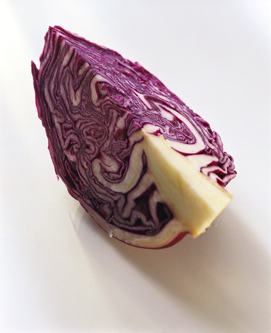 A quarter of a red cabbage on white background