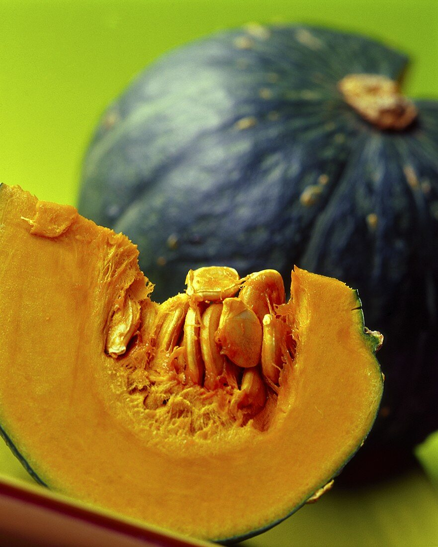 Wedge of pumpkin in front of pumpkin with piece cut out