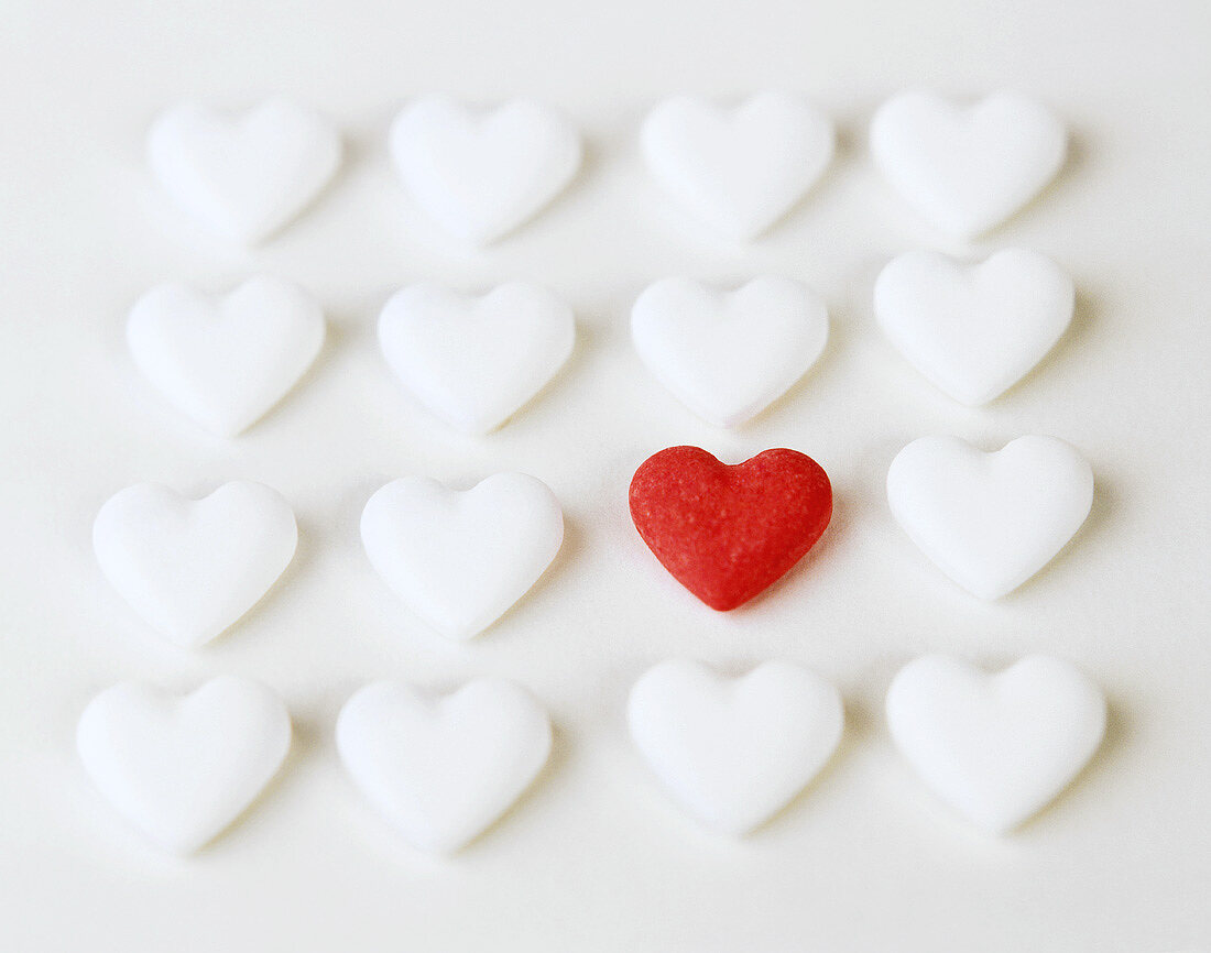Grape sugar hearts, several white and one red