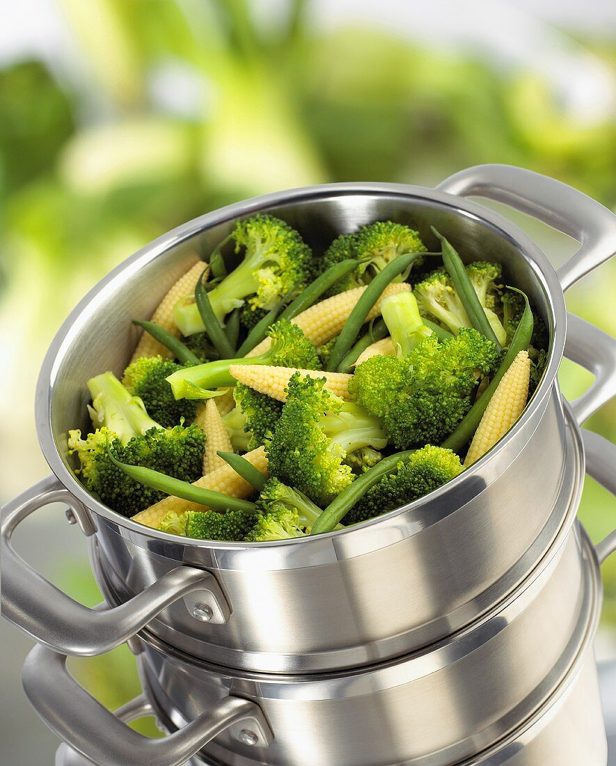 Broccoli, baby corn-cobs and green beans in steaming pan