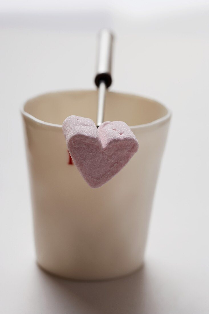 A heart-shaped marshmallow on a fondue fork resting on a mug