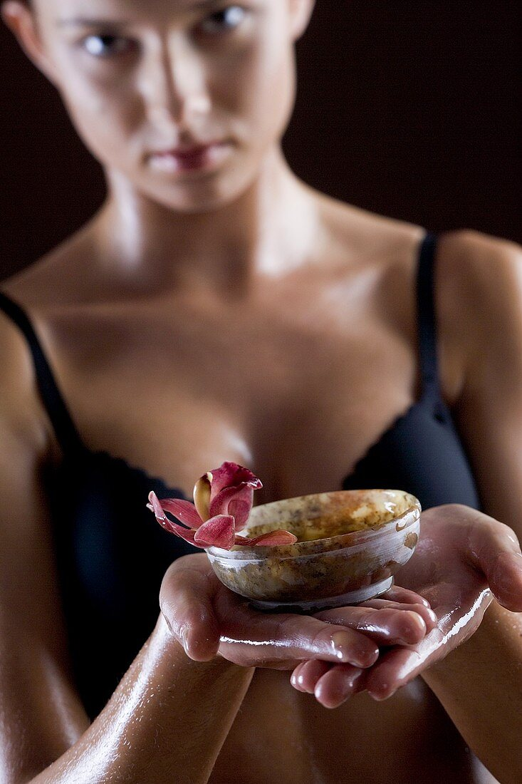 Young woman holding small bowl of body butter with orchid