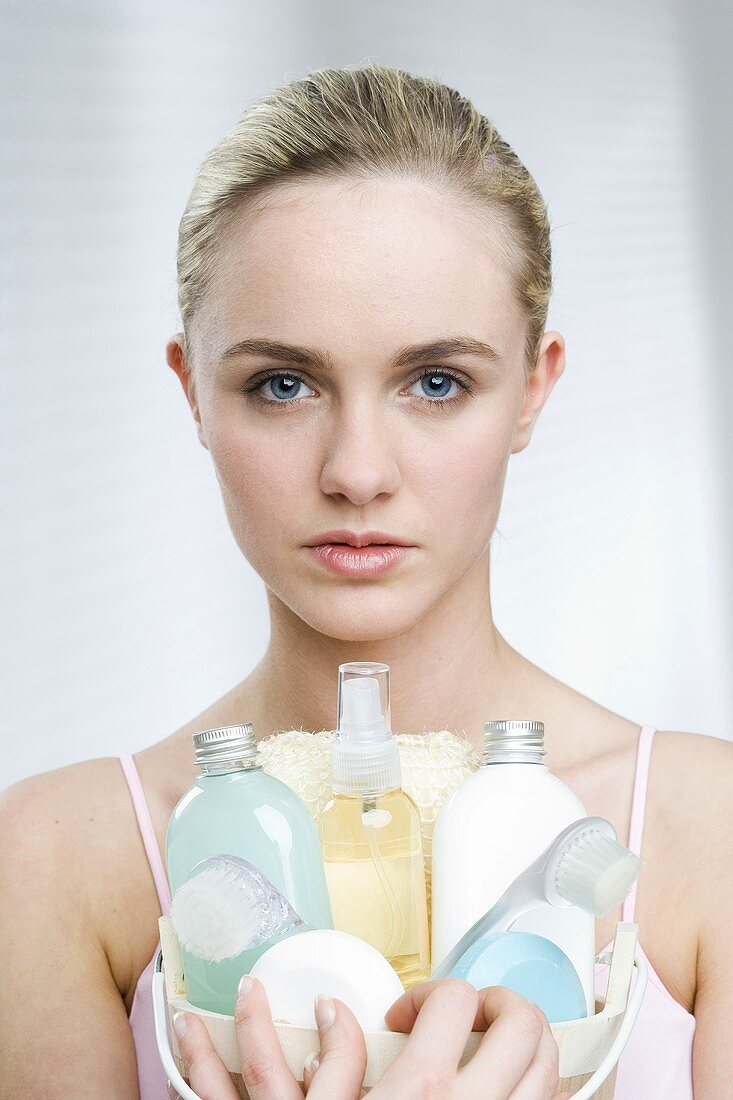 Young woman holding a basket of cosmetics