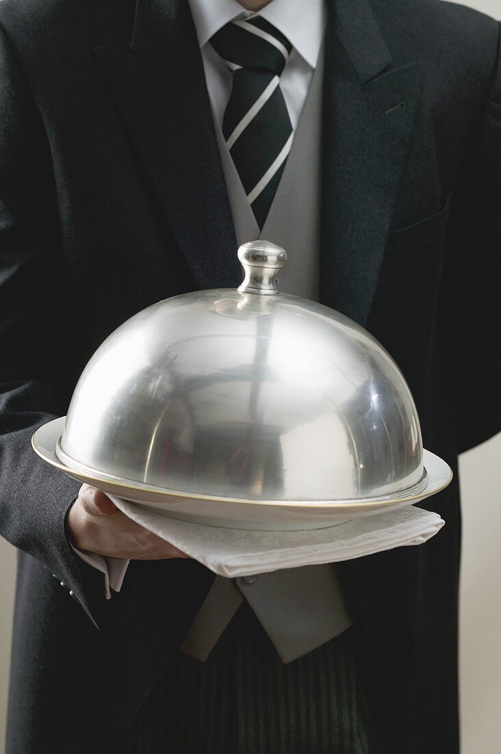 Waiter serving dish under dome cover