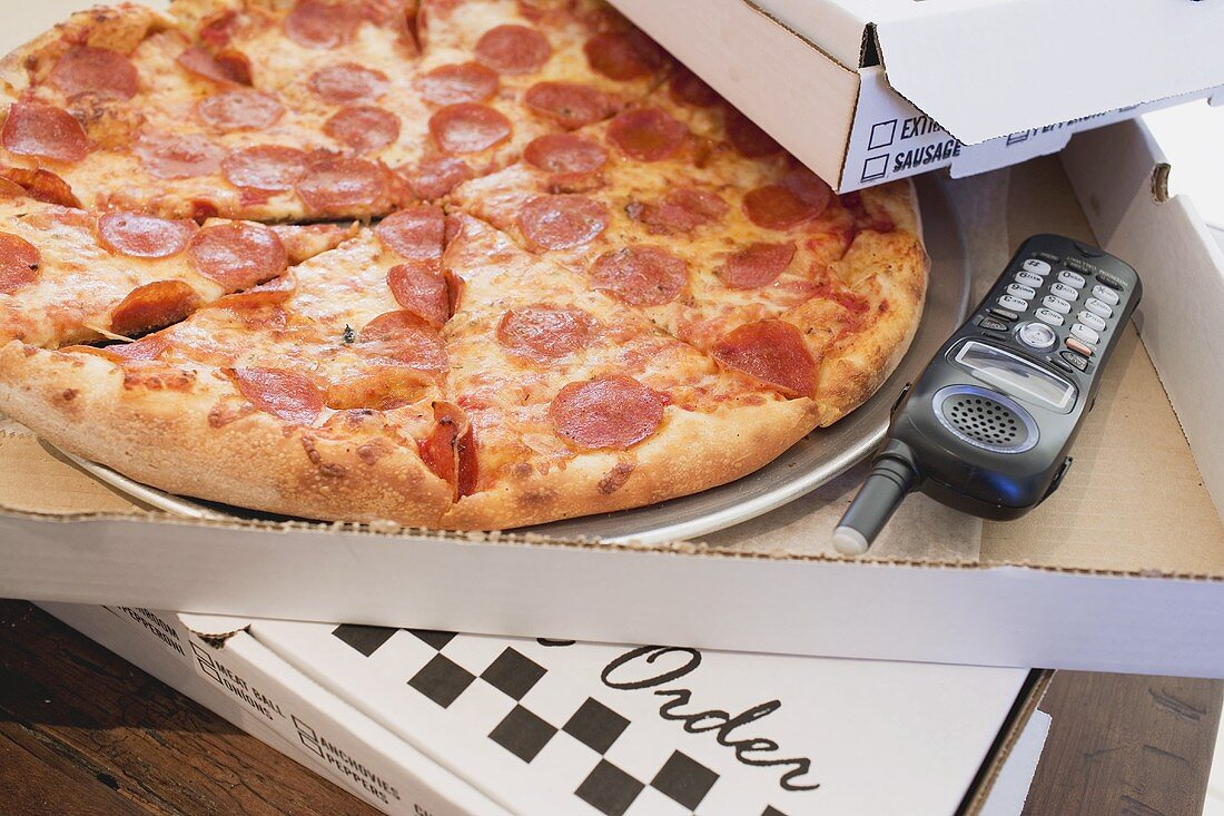 Pepperoni pizza in pizza box, telephone beside it