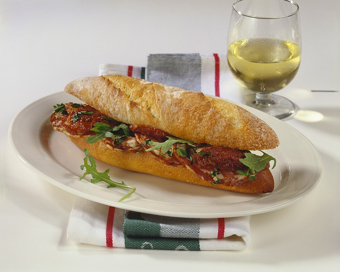 Baguette roll filled with salami, dried tomatoes & rocket