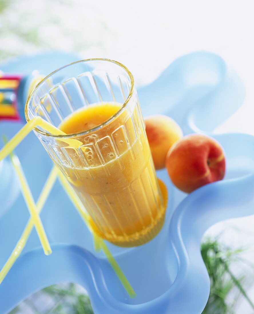 A glass of peach nectar with straw