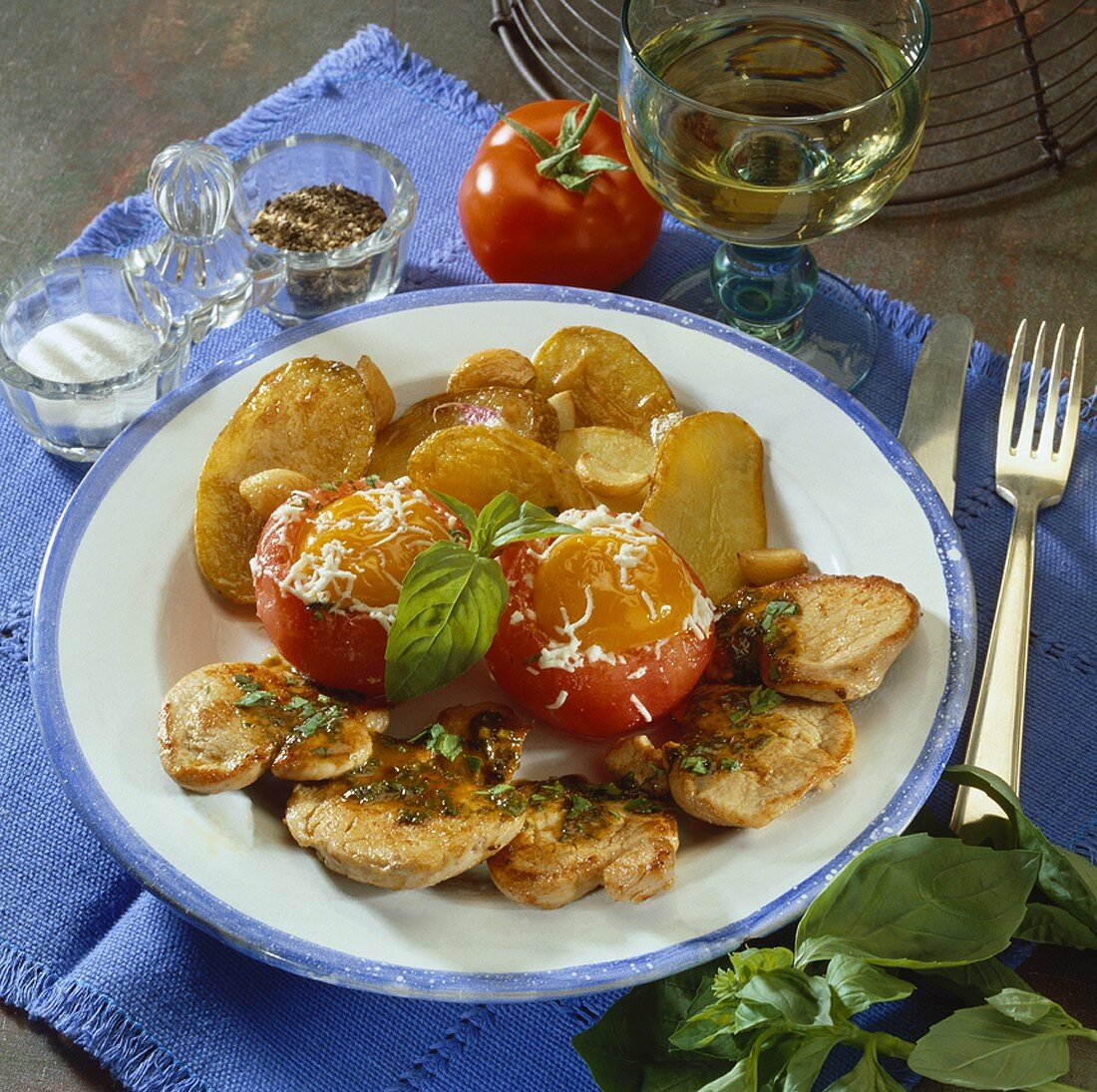 Pork fillet, eggs in tomato nests and fried potatoes
