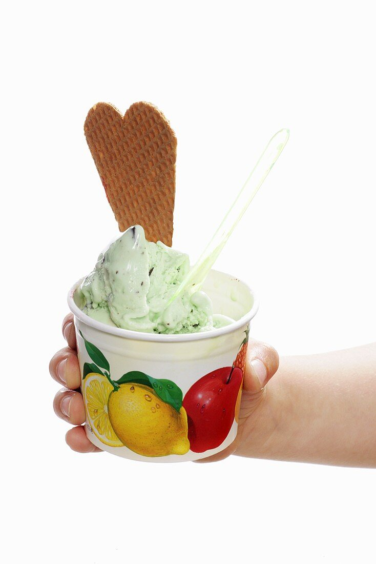 Hand holding a tub of peppermint ice cream, spoon & wafer