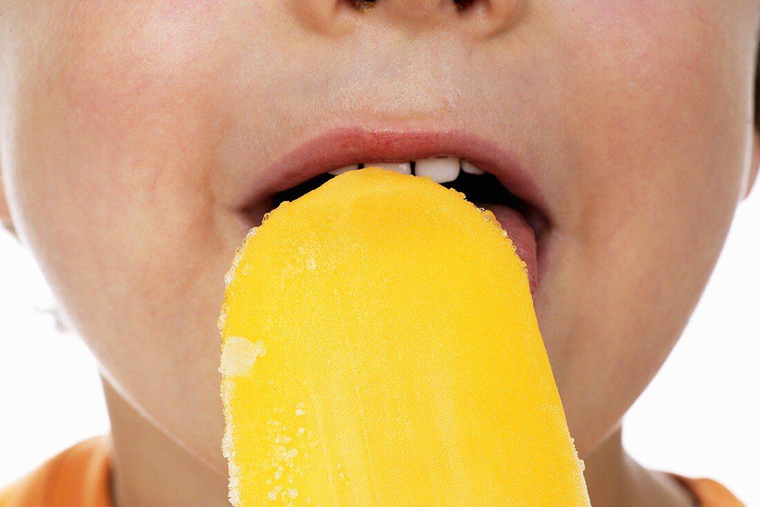 Boy eating orange ice lolly (close-up)