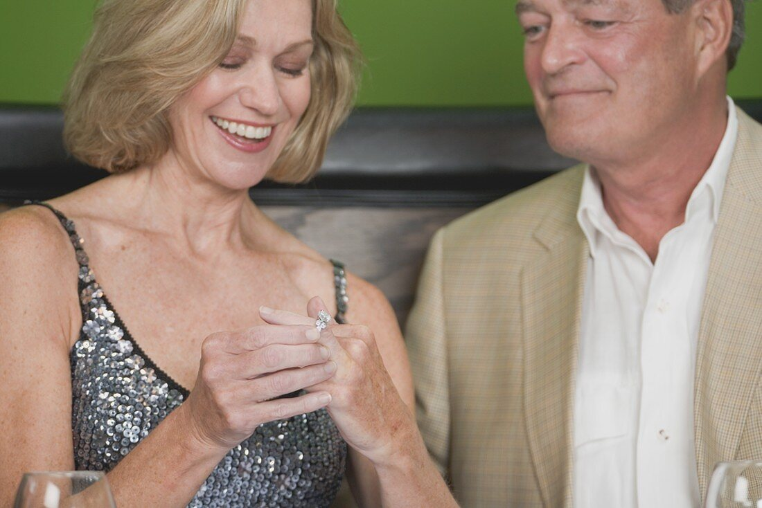 Mature woman happily trying on engagement ring