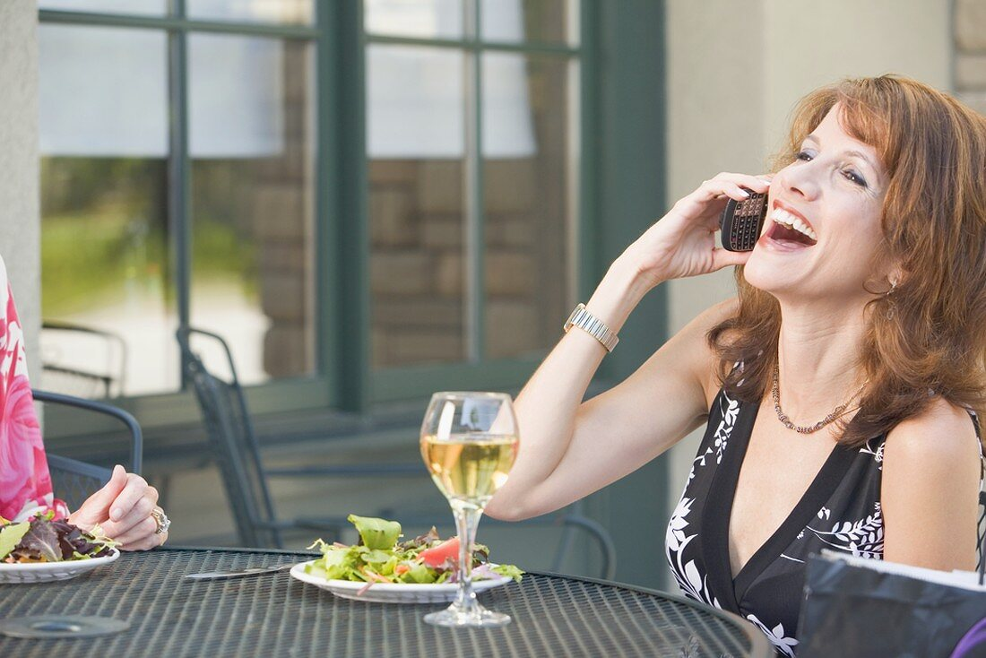Brunette on phone at laid table on terrace