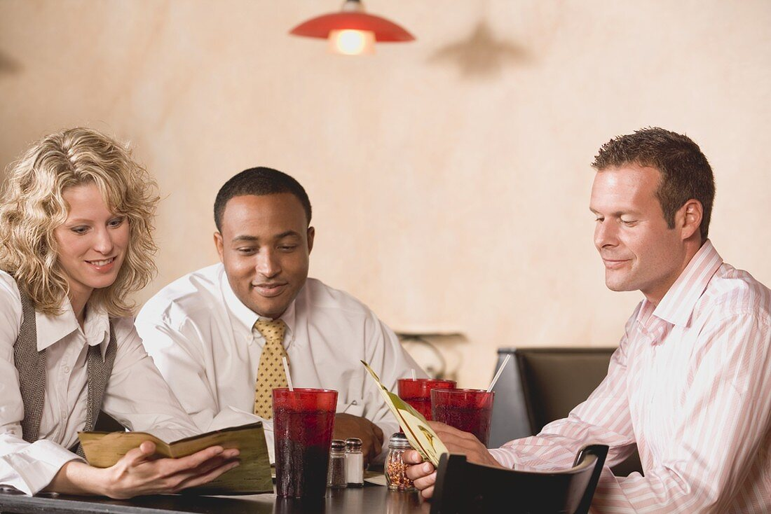 Three people at a restaurant table reading the menu