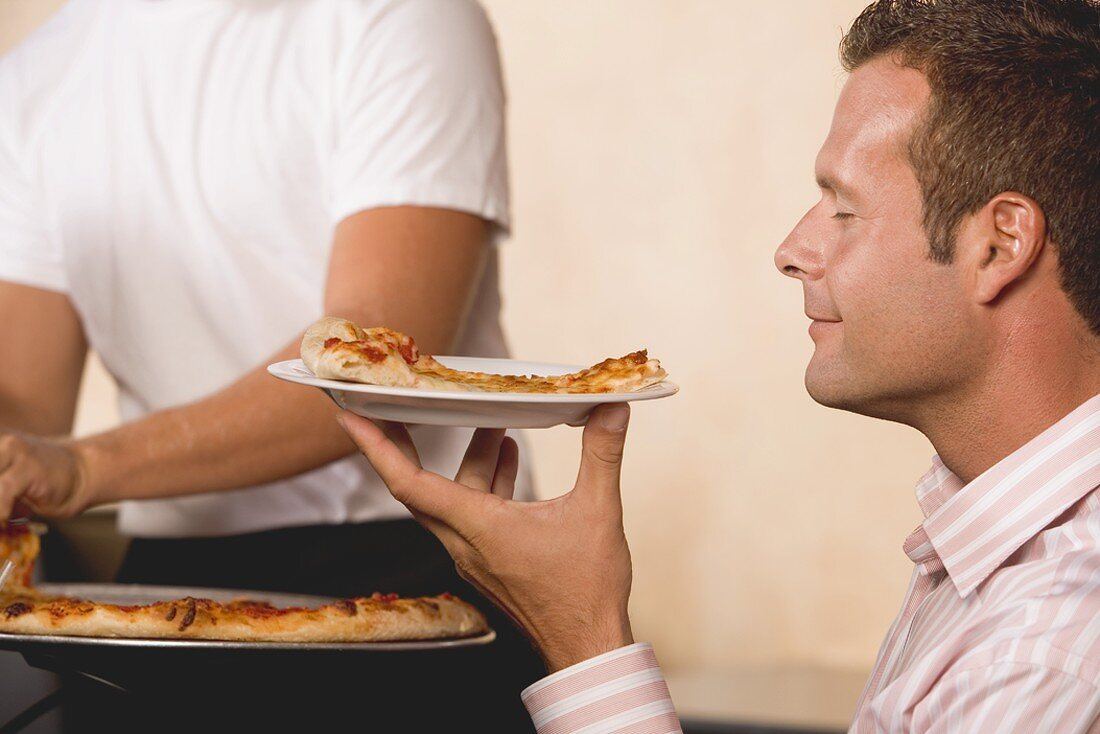 Man with contented expression holding slice of pizza on plate