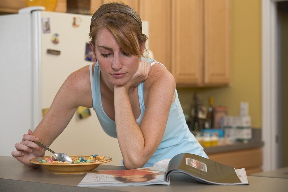 Young woman eating fruit-flavoured cereal loops, reading newspaper