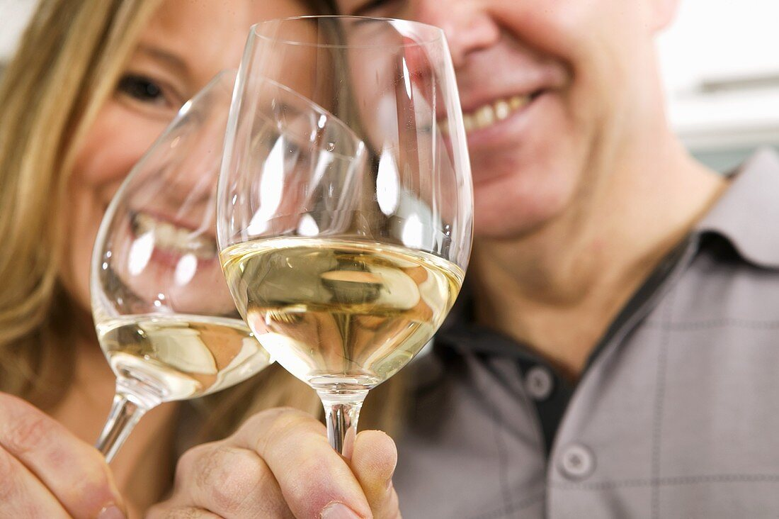Man and woman clinking glasses of white wine together