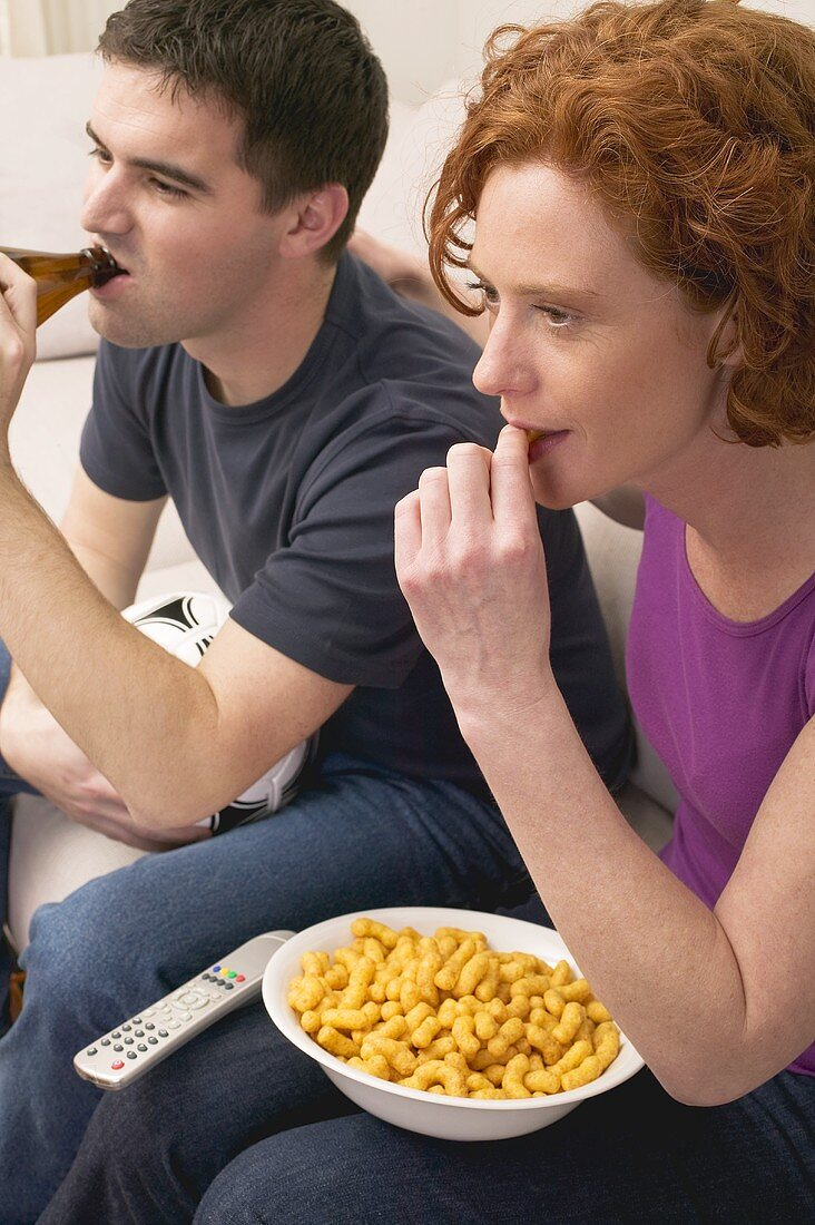Young couple with football, beer and snack food watching TV