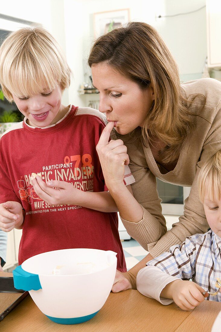 Mother and son tasting baking mixture