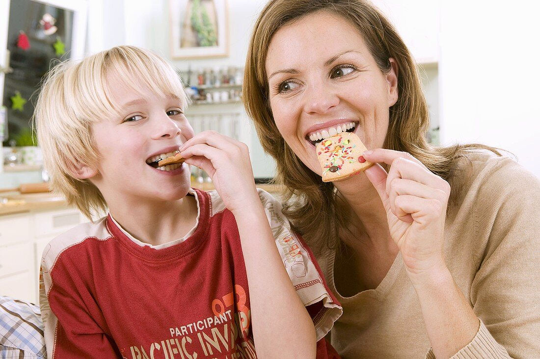 Mother and son eating Christmas biscuits