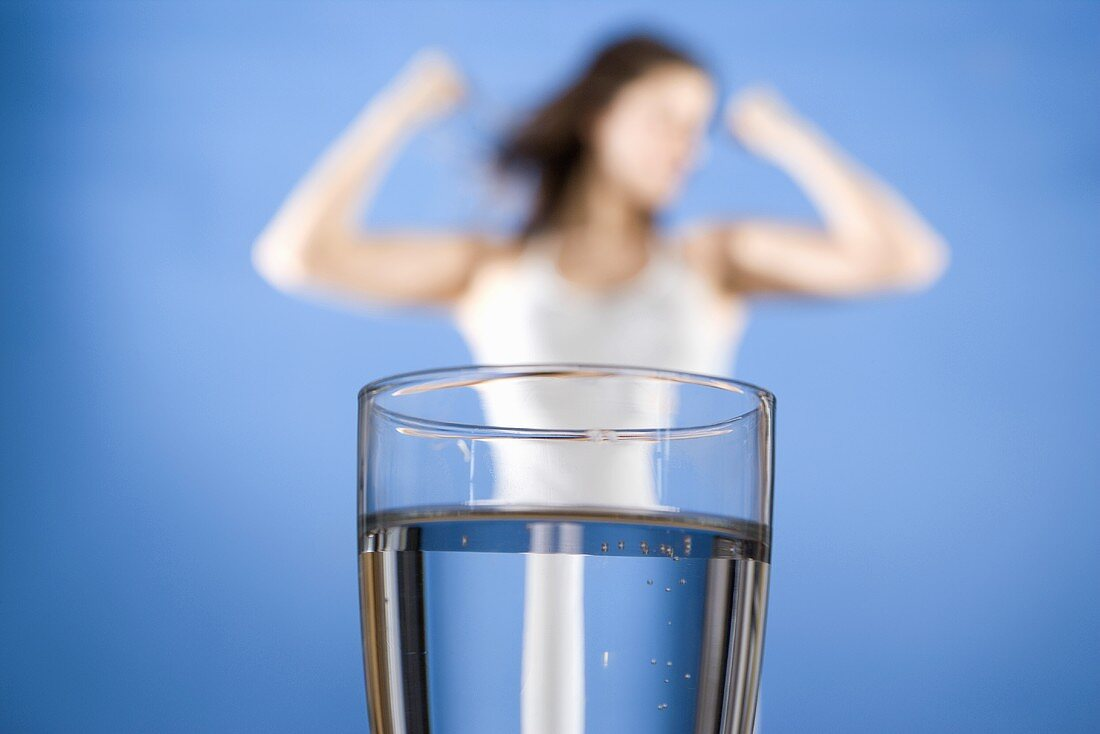 Glass of water, slim woman flexing her muscles in background