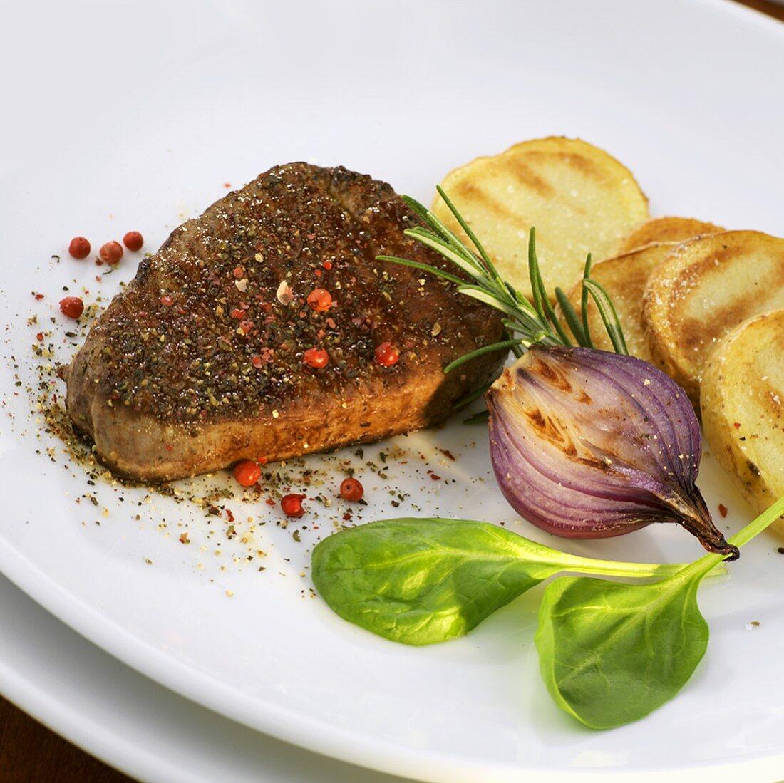 Peppered steak with potato slices and onion