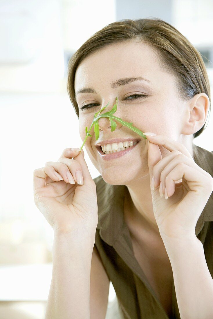 Young woman holding rocket leaf across her nose
