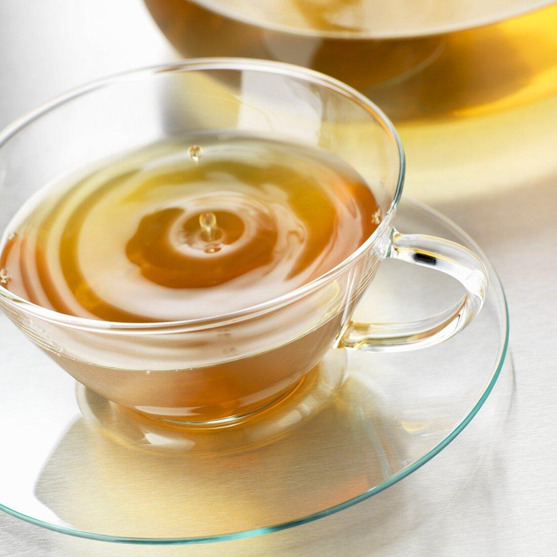 Drop of tea falling into a cup of tea