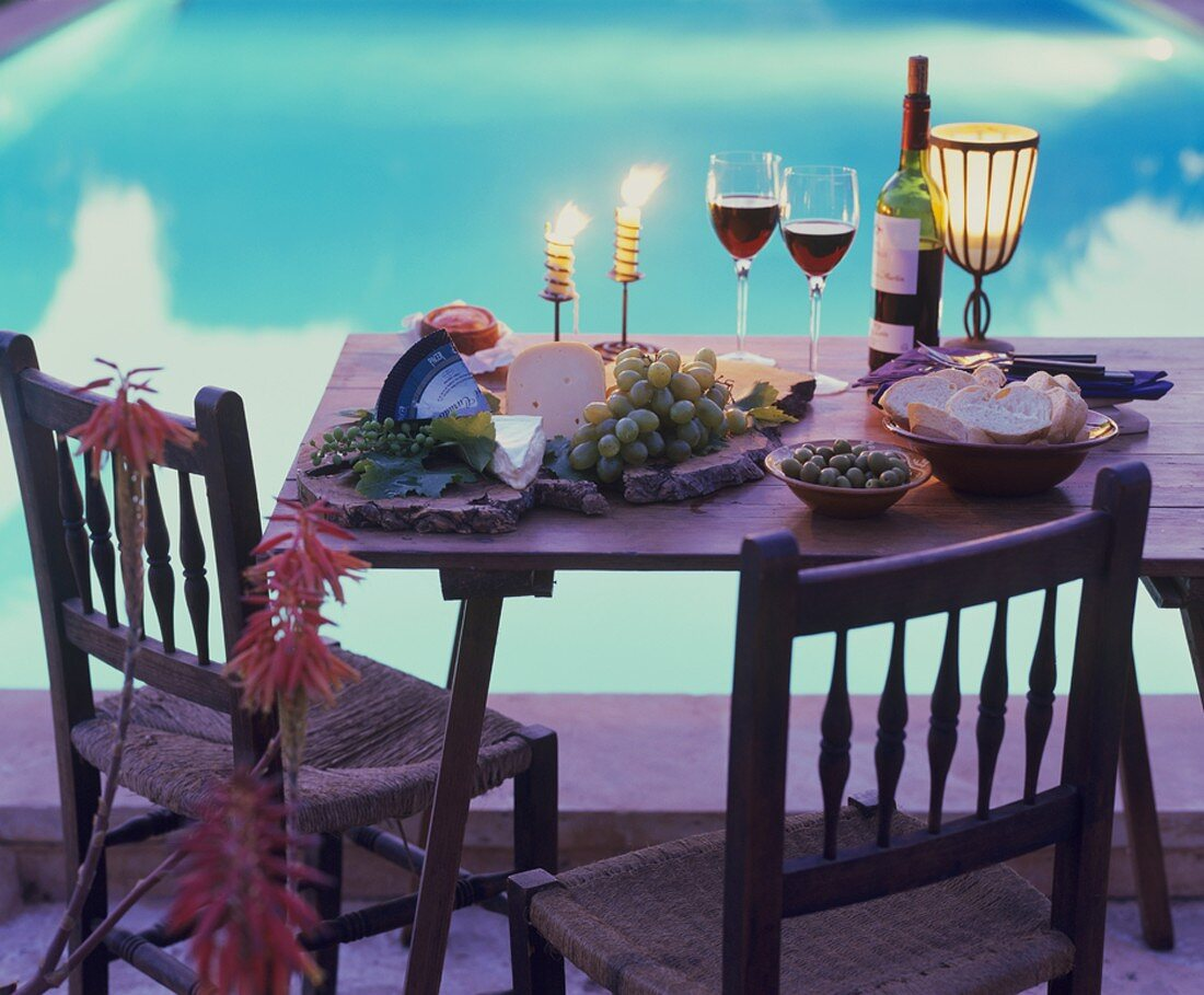 Cheese board, olives, white bread & red wine on table by pool