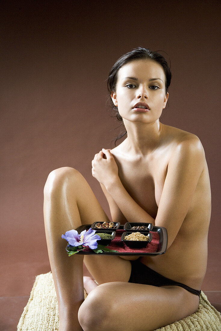 Woman holding a tray of spices (for spice body treatment)