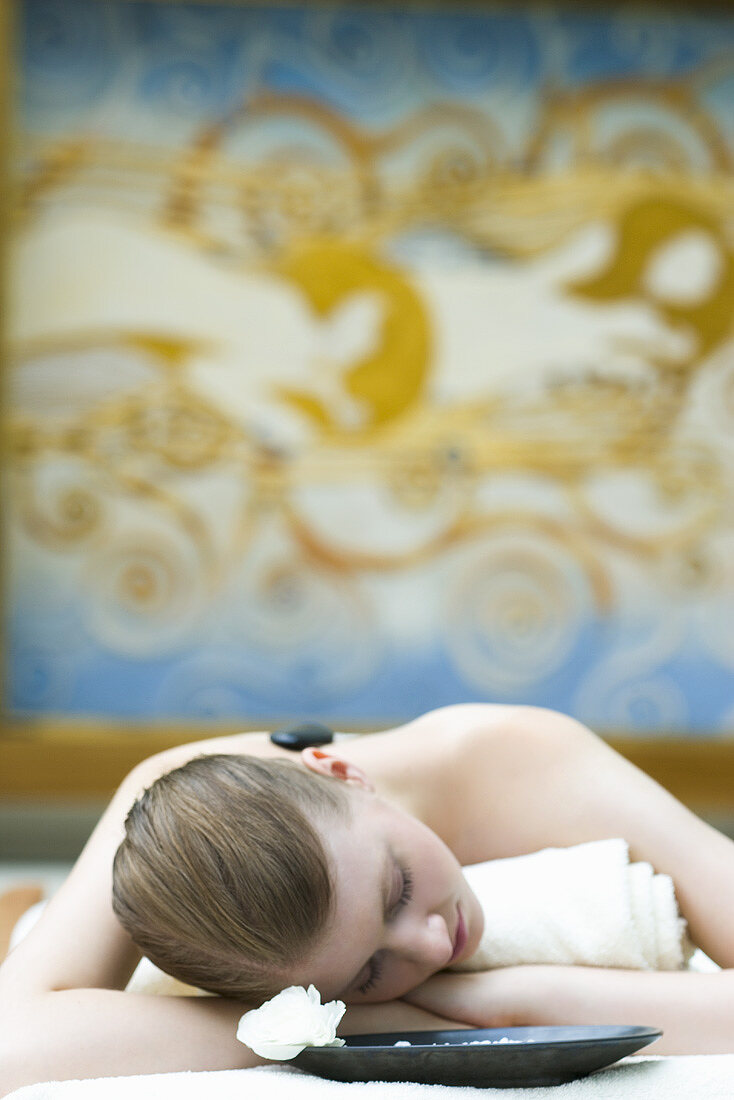 Young woman having LaStone Therapy (hot & cold stone massage)
