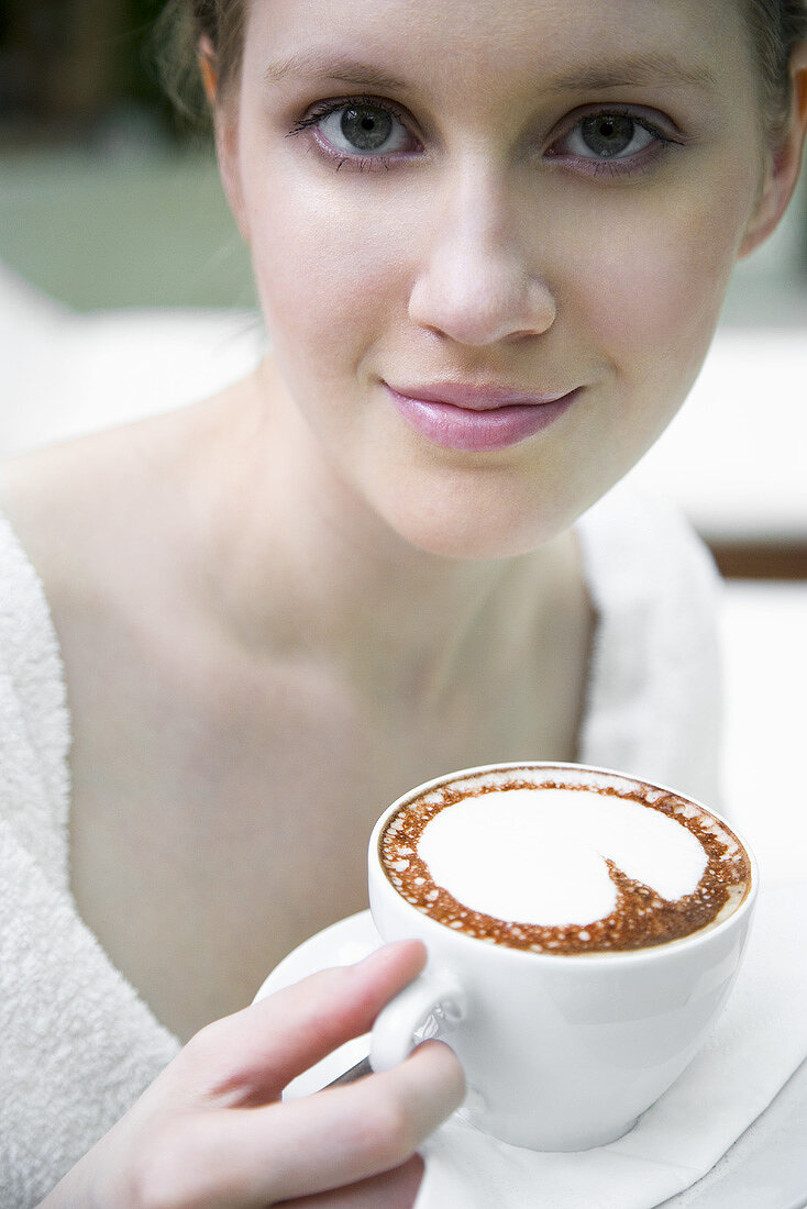 Young woman in bathrobe drinking cappuccino
