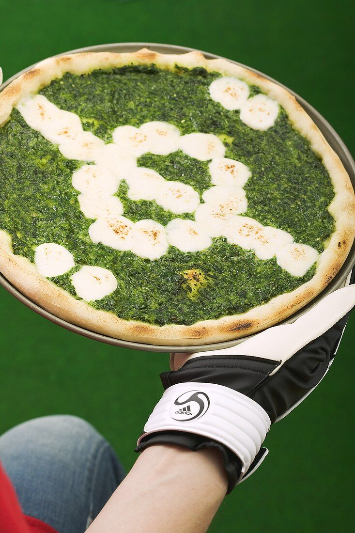Spinach pizza representing football pitch