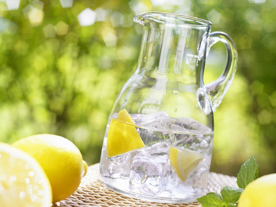 Glass jug of mineral water with lemon wedges and ice cubes