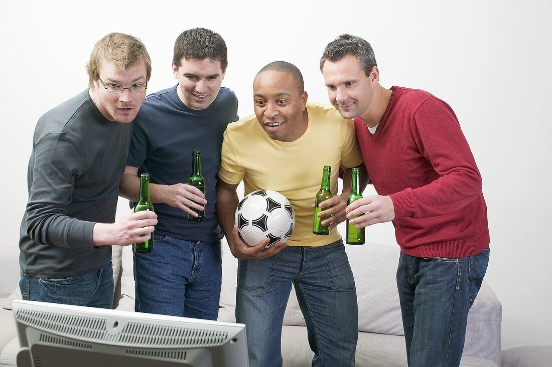 Four men with bottles of beer and football in front of TV