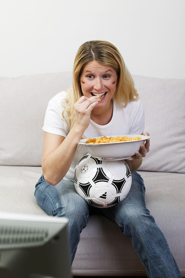 Young woman with football and snack food watching TV