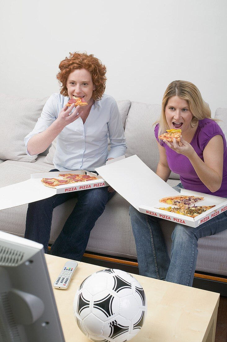 Two friends eating pizza while watching TV