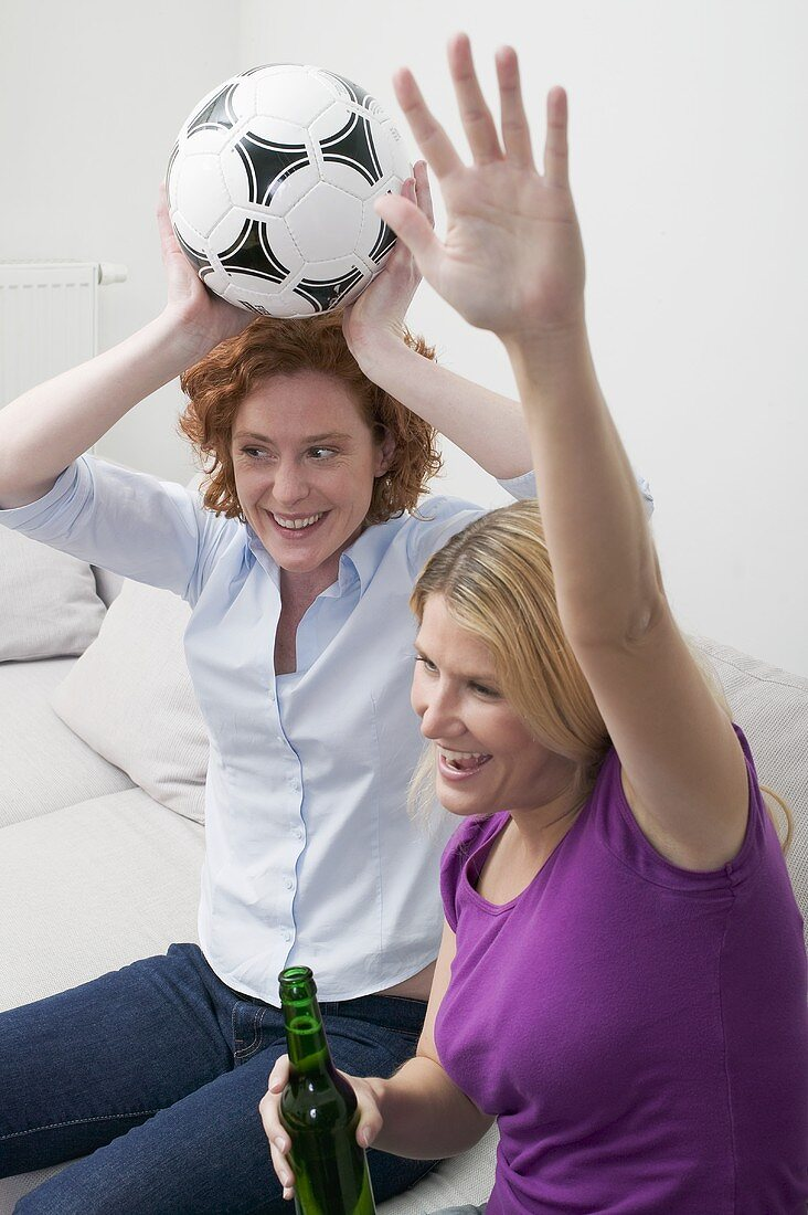 Two friends cheering with football and beer