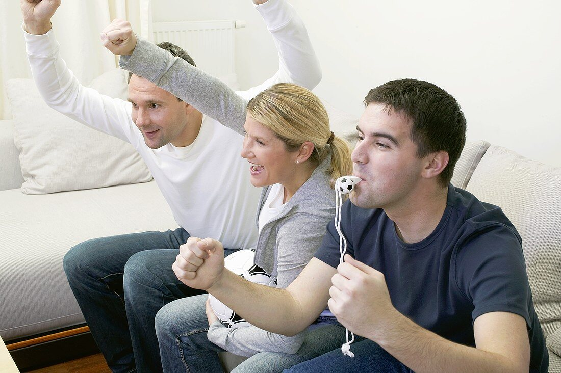 Friends with whistle & football cheering in front of TV