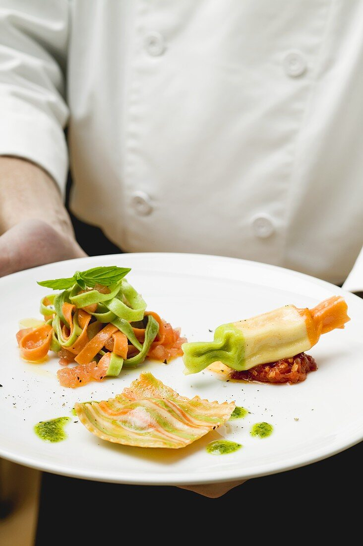 Chef holding plate of coloured pasta