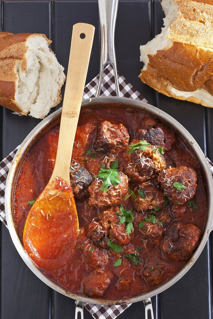 Pot of Homemade Meatballs in Sauce with Parsley; Wooden Spoon; Bread
