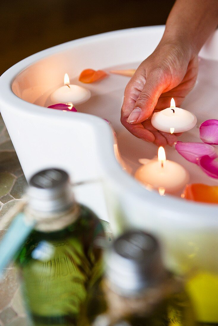 A rose petal bath with floating candles and massage oils