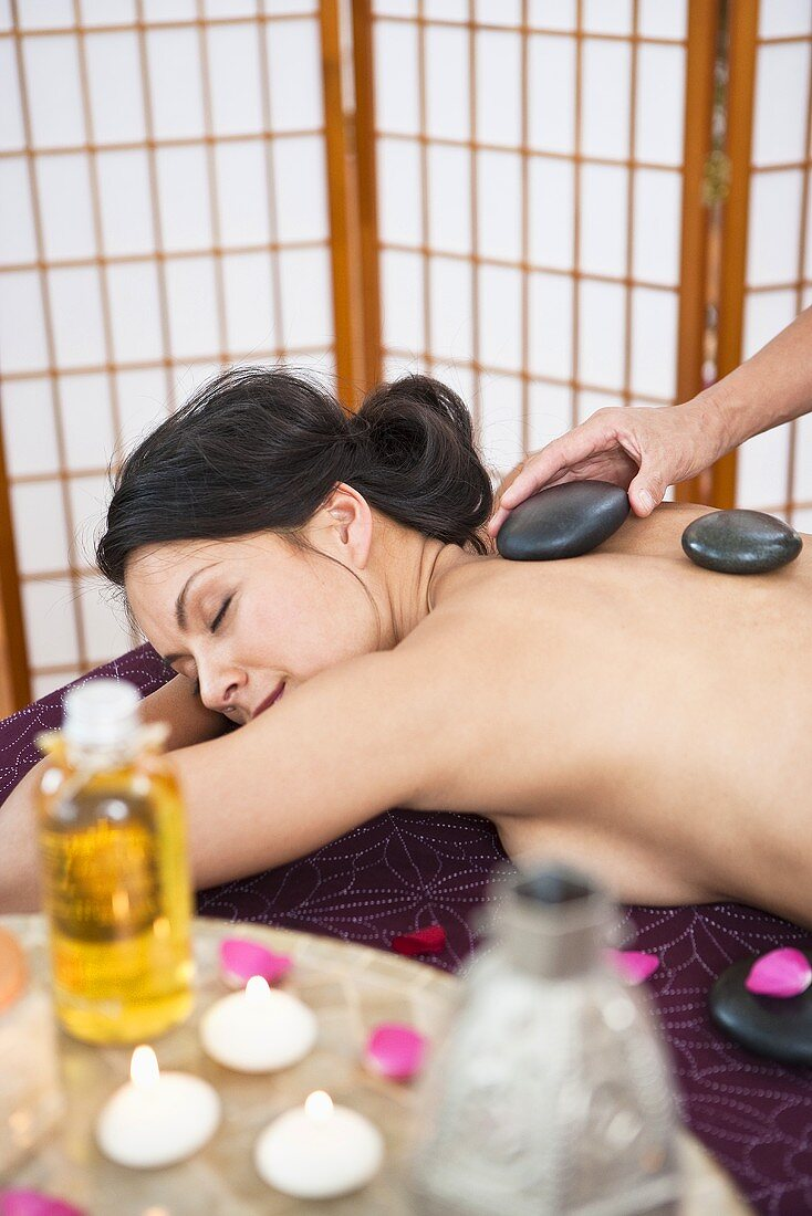 A woman having a La Stone massage in a spa
